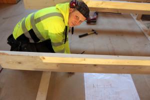 Erik Svensson sågar till en rejäl öppning för den bashögtalare som ska installeras i scengolvet. Foto: Hans Andersson