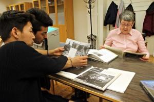 Morteza och Sohrab kikar på gamla fotografier tillsammans med Ann-Marie Lindkvist. Foto: Ida Lindkvist