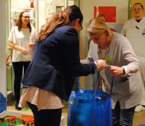 Verksamhetschef Lena Göransson tar emot en av de nio kassarna med leksaker. Foto: Maria Andréasson, Region Örebro Län