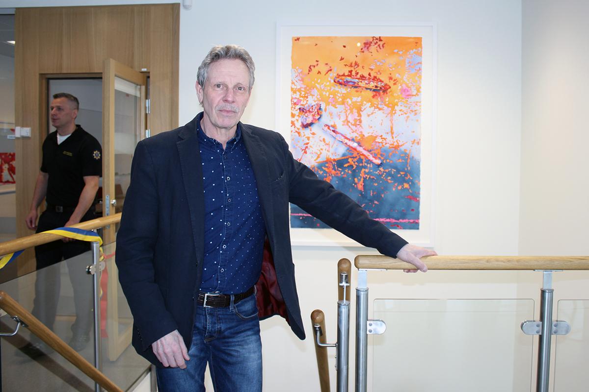 """Thomas Rydén framför  den stora akvarellmålningen i trappan. """"Järnbitar"""" är gjord utifrån storlek och inredning."""